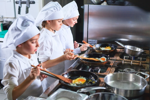Enfants préparant le déjeuner dans une cuisine de restaurant.