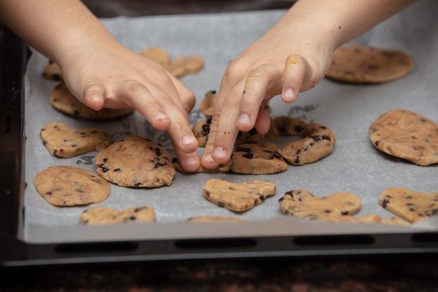Les enfants préparent des biscuits dans la cuisine de la maison. gros plan sur les mains de l'enfant préparant des cookies à l'aide de cookies.