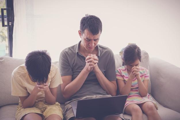 Enfants priant avec le père devant l'ordinateur portable