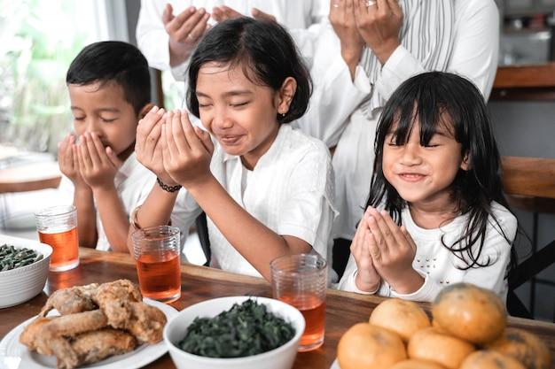 Les enfants prient le bras ouvert musulman