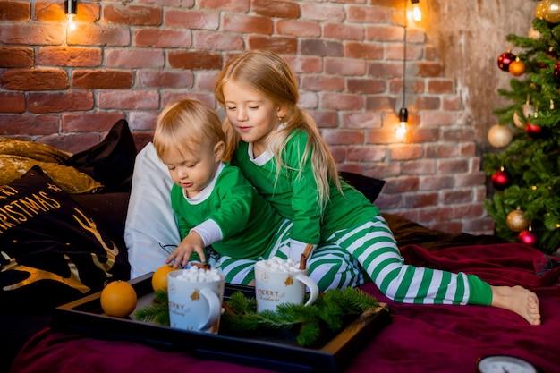 Enfants en pyjama ayant du cacao près de l'arbre de noël