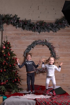 Enfants en pyjama jouant à la maison le soir des vacances de noël. heureux enfant sautant sur le lit.