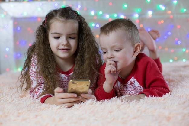 Enfants en pyjama de noël jouant smartphone