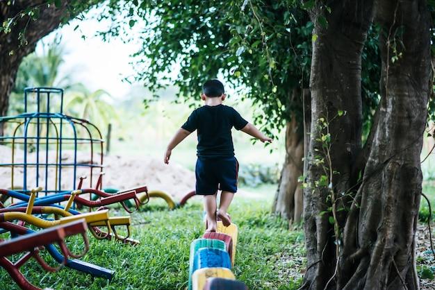 Des enfants qui courent sur des pneus dans la cour de récréation.