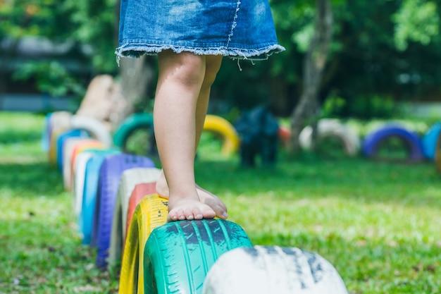 Enfants qui courent sur des pneus dans la cour de récréation