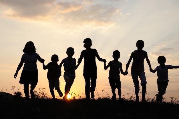 Enfants qui courent sur prairie au coucher du soleil