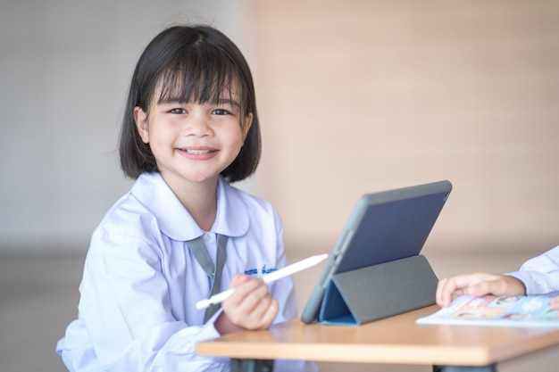 Les enfants qui retournent à l'école étudient ensemble à l'aide d'une tablette numérique et écrivent sur un ordinateur portable à l'école