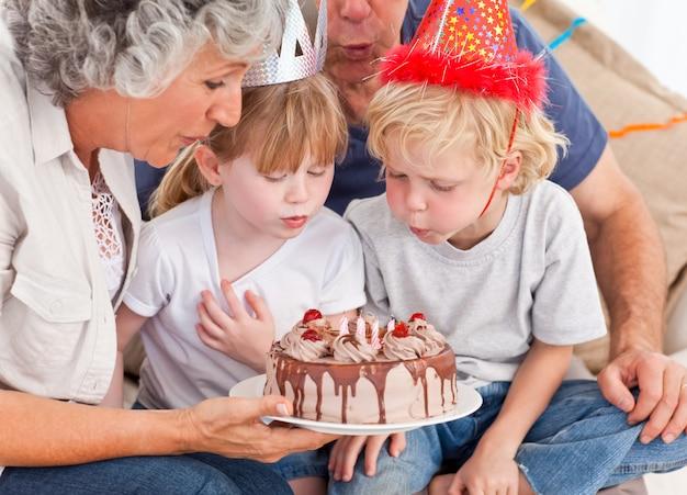 Enfants qui soufflent sur le gâteau d'anniversaire