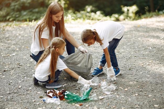 Enfants ramassent les ordures dans des sacs à ordures dans le parc