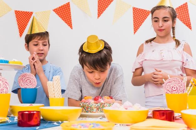 Enfants regardant leur ami soufflant des bougies d'anniversaire