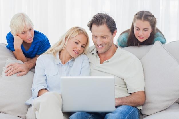 Enfants regardant les parents à l'aide d'un ordinateur portable