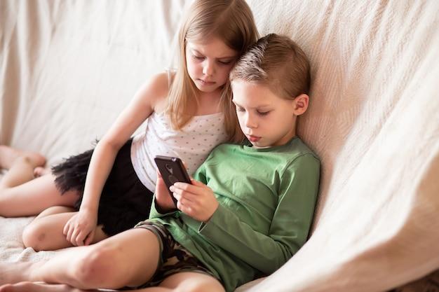 Enfants regardant des vidéos sur des gadgets allongés sur le canapé