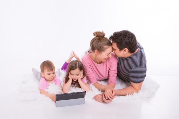 Les enfants regardent des dessins animés sur la tablette. un homme et une femme s'embrassent. vacances en famille, passe-temps commun. parents avec des filles sur le sol