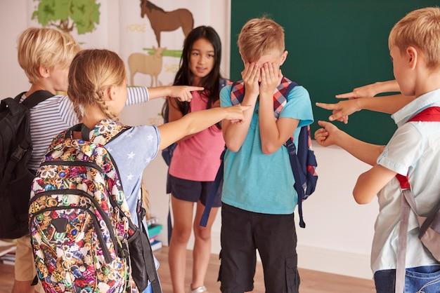 Les enfants rient de leur camarade de classe