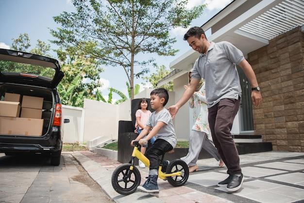 Les enfants roulent à vélo poussé par son père