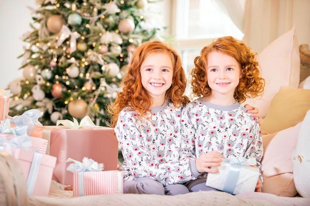 Enfants rousses en pyjama assis sur le lit avec des cadeaux dans leurs mains contre l'arbre de noël.