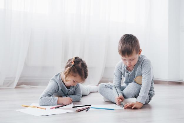 Les enfants s'allongent sur le sol en pyjama et dessinent avec des crayons. peinture d'enfant mignon par des crayons.