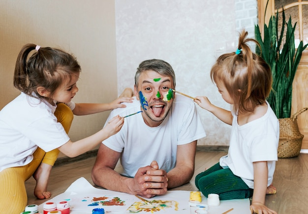 Les enfants s'amusent avec leur père, les filles dessinent sur la peau du visage d'un homme avec des peintures colorées, la créativité et l'imagination de la fête des pères et le concept de la famille