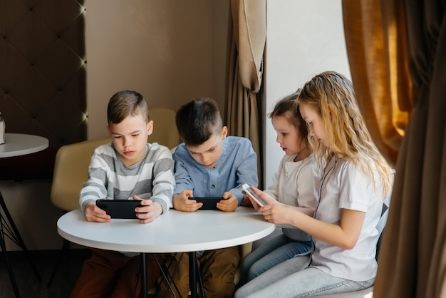 Les enfants s'assoient à une table dans un café et jouent ensemble au téléphone portable. divertissement moderne.