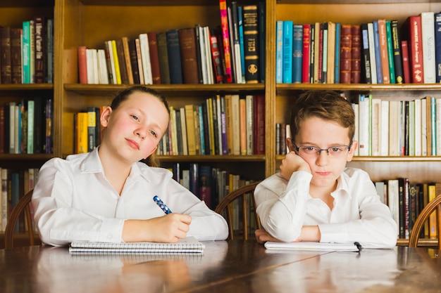 Enfants s'ennuie assis dans la bibliothèque avec des cahiers