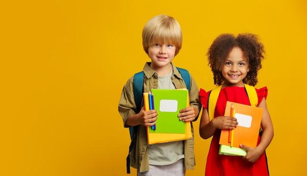 Les enfants avec des sacs à dos d'école regardent la caméra, tenant des livres et des crayons dans leurs mains