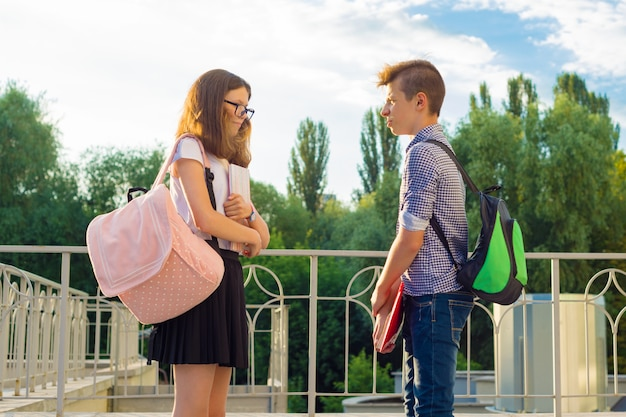 Les enfants avec des sacs à dos, des manuels, des cahiers vont à l'école