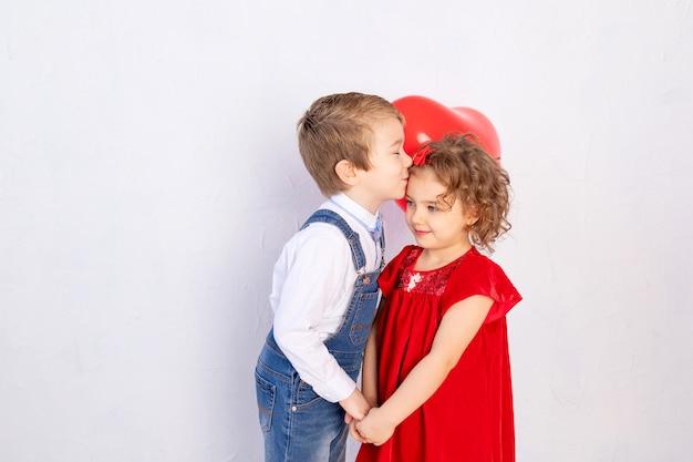 Les enfants de la saint-valentin. garçon bisous fille de cinq ans tenant coeur de boule rouge