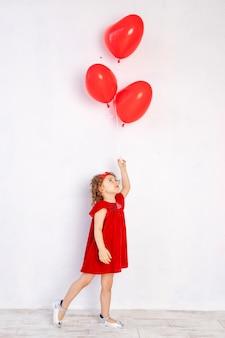 Les enfants de la saint-valentin. petite fille en robe rouge tenant des ballons en forme de coeur