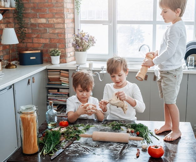 Enfants sales et jeunes vêtus de vêtements décontractés apprenant à cuisiner et jouant avec de la farine dans une cuisine moderne par beau temps.