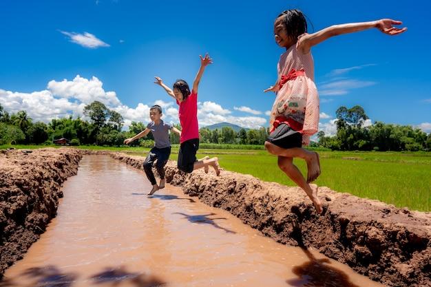 Les enfants sautent à l'eau et éclaboussent l'eau de jouer en milieu rural sur fond de ciel bleu et rizière