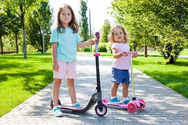 Enfants sur un scooter dans le parc sur une journée d'été ensoleillée. activité amusante pour enfant