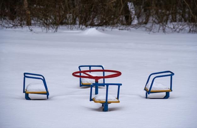 Les enfants se balancent recouverts de neige dans le parc.