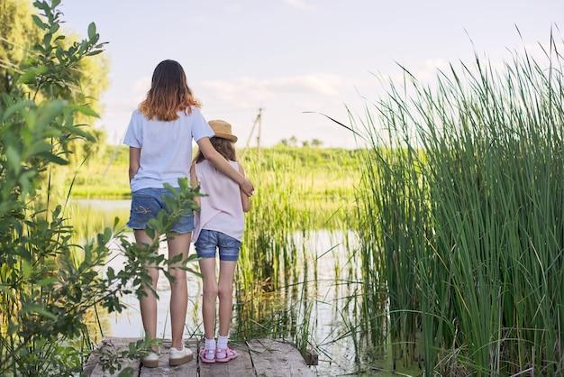 Enfants se reposant près de l'eau aux beaux jours d'été, deux filles regardant le lac sur le pont, se détendre, copier l'espace, vue arrière