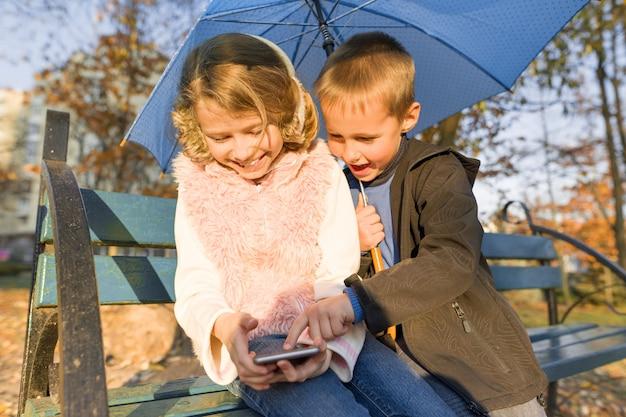Enfants, séance banc, dans, automne, parc, utilisation, smartphone