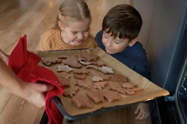 Enfants sentant les biscuits au pain d'épice fraîchement cuits