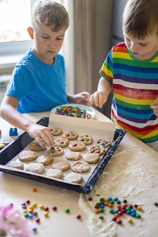 Enfants de sexe masculin drôles de frère se réjouissant de s'amuser à cuisiner un dessert avec des chocolats ronds multicolores mm