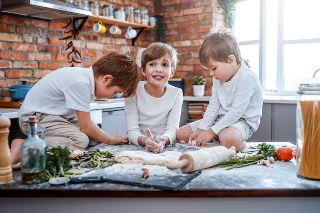 Des enfants de sexe masculin joyeux dans la cuisine font cuire des pizzas à l'aide d'équipements de cuisine préparant des légumes avec de la pâte.