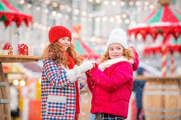 Des enfants, des sœurs rousses se réchauffent les mains gantées avec une tasse de thé chaud sur un marché de noël décoré de façon festive dans la ville.