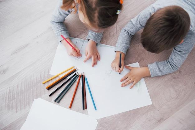 Les enfants sont allongés par terre en pyjama et dessinent avec des crayons. enfant mignonne peignant avec des crayons