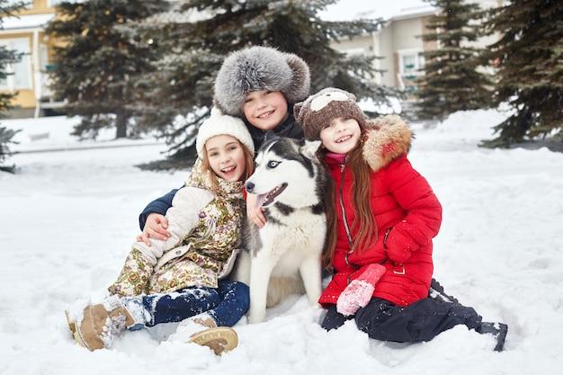 Les enfants sont assis dans la neige et caressent le chien husky. les enfants sortent et jouent avec un chien husky en hiver