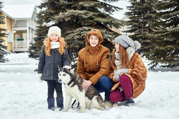 Les enfants sont assis dans la neige et caressent le chien husky. les enfants sortent et jouent avec un chien husky