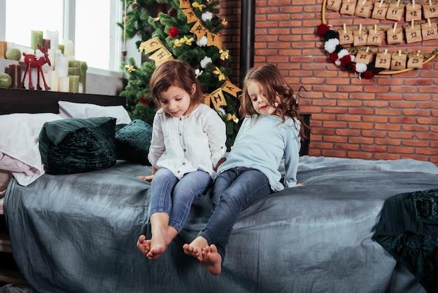Les enfants sont assis sur le lit avec des objets décoratifs. conception du nouvel an.