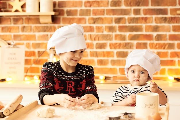 Les enfants sont cuits et jouent avec de la farine et de la pâte dans la cuisine