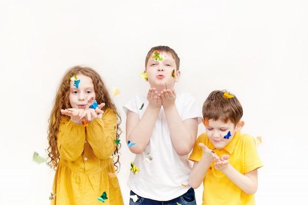 Enfants soufflant des confettis sur fond clair.