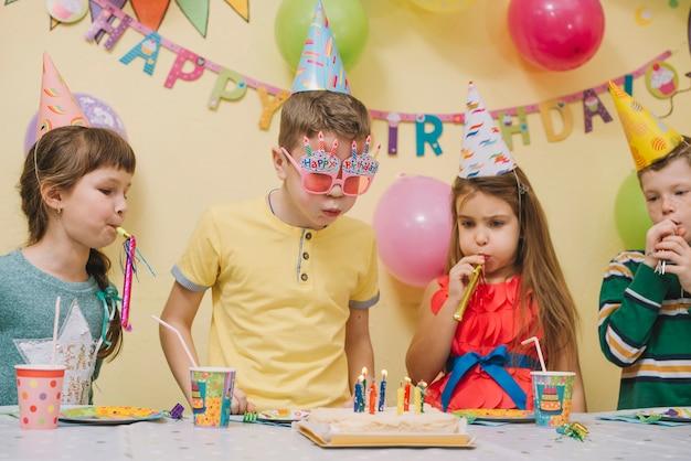 Enfants soufflant des cornes et des bougies sur le gâteau