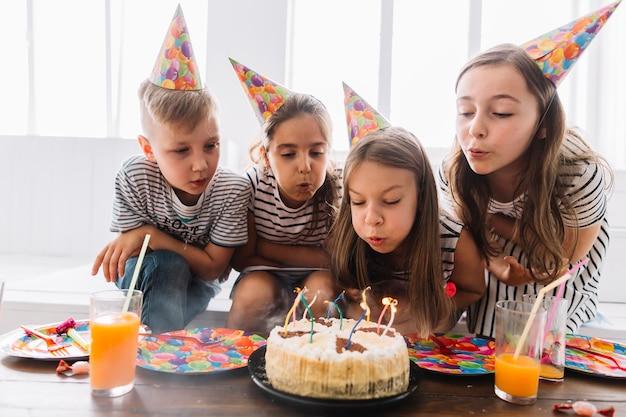 Enfants soufflant ensemble des bougies d'anniversaire