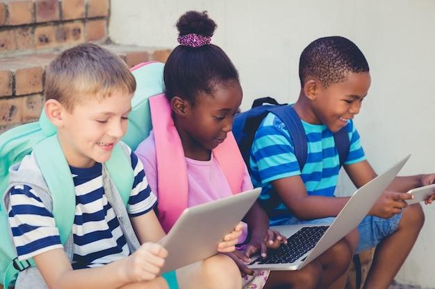 Enfants souriants à l'aide d'un ordinateur portable et d'une tablette numérique dans les escaliers