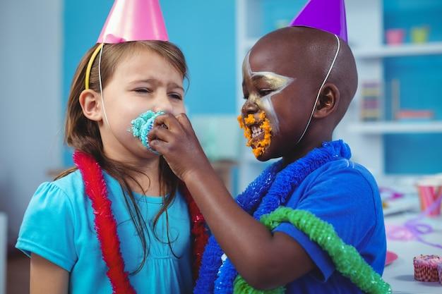 Enfants souriants avec glaçage sur leurs visages