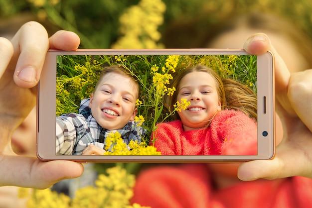 Enfants souriants heureux faisant autoportrait sur smartphone dans la prairie.