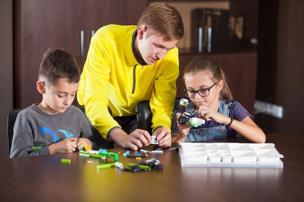 Des enfants souriants et joyeux construisent un constructeur.